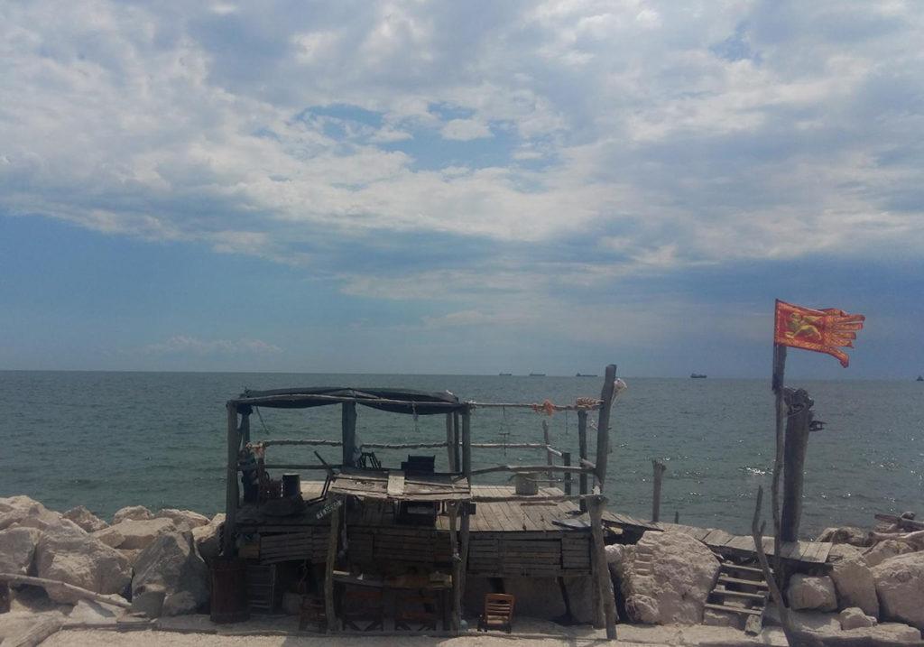 Самодельные хижины на одном из пляжей острова Лидо и флаг Венеции